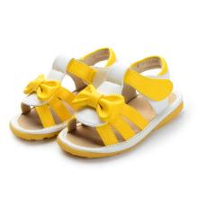 Sandálias de bebê amarelo com uma linda arco