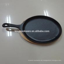 Gusseisen brutzelnder Steakpfanne / heiße Platte mit Holzbrett