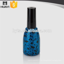 botella azul oscuro vacía del esmalte de uñas del gel del uv