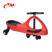 Plastikbabyschwingenauto, das Spielzeugauto / klassische Fahrt auf Auto für Kinder / glückliches Kinderschwingenauto fährt