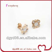 Chica fresca y alegre con pendientes de acero inoxidable en forma de flor, pendientes de oro para las mujeres