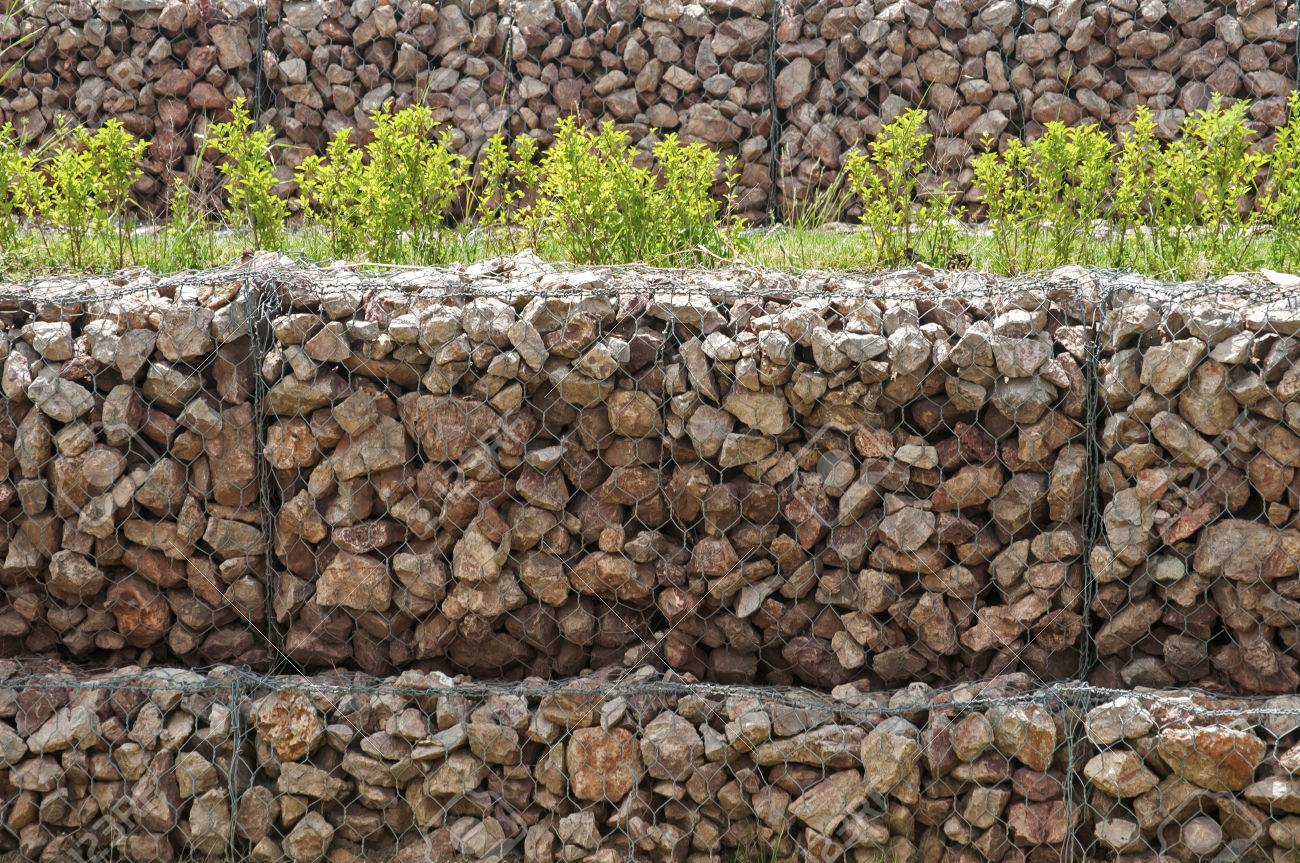 61128801-hexagonal-wire-netting-gabion-box-wall-filled-with-stones-closeup-as-background