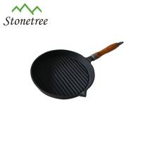 Plaque de cuisson ronde en fonte avec manche en bois