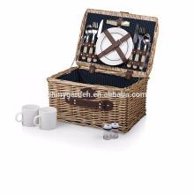 Canasta de picnic de ratán con tazas, cucharillas, placa de cerámica, olla de sal y pimienta