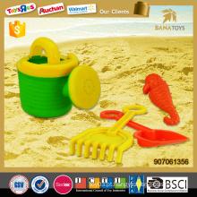 Lata molhando ao ar livre com a pá eo jogo da praia do molde