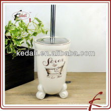white ceramic and decal toilet brush with base