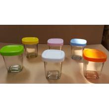 Tarro de cristal con leche vidrio con tapas de diferentes colores