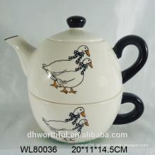 Keramische Teekanne im Entenabziehbild mit Tasse