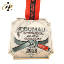 Custom DUMAN medallion metal jiujitsu medal with red ribbon