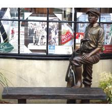 escultura de bronce al aire libre de tamaño natural de un carrito con un banco