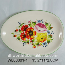 Oval ceramic serving platter with flower and bird decal