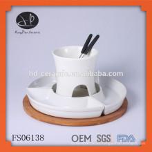 Una pieza de fondue de chocolate de porcelana para 4 personas, fondue con base de madera