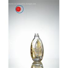 Botella de vidrio de forma redonda con etiqueta dorada