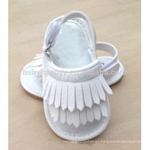 El niño vendedor caliente de los moccasines de los cabritos calza los zapatos de la sandalia del bebé