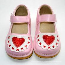 Sapatas cor-de-rosa do bebé com coração vermelho
