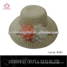 Meninas que decoram chapéus de palha dobráveis