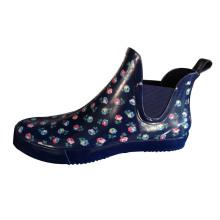 Zapatos del jardín del caucho de la muchacha