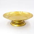Runder, runder, goldfarbener Edelstahl-Teller mit Obstauflage