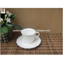 Weiße keramische Schale und Untertasse mit einfachem Abziehbild Goldrand