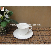 white ceramic cup and saucer with simple decal gold rim