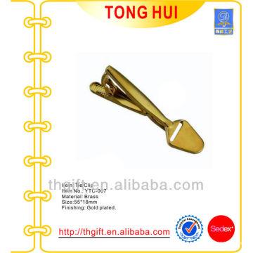 O empate em forma de pá de ouro metálico com logotipo em branco