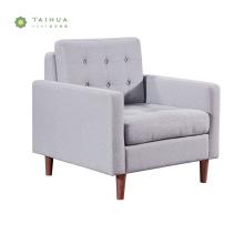 Sofá de tecido cinza com assento único e pernas