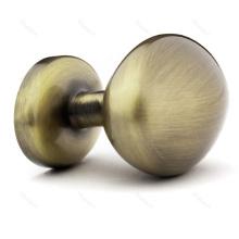 Manija y botón antiguos de latón de la puerta del armario de cocina