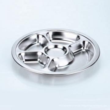em volta da prata de aço inoxidável de 3 seções que serve a bandeja do alimento do almoço para a cantina da escola