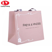Pink paper gift bag with ribbon handle