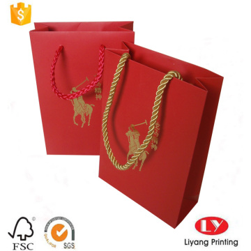 Red paper gift bag with gold logo