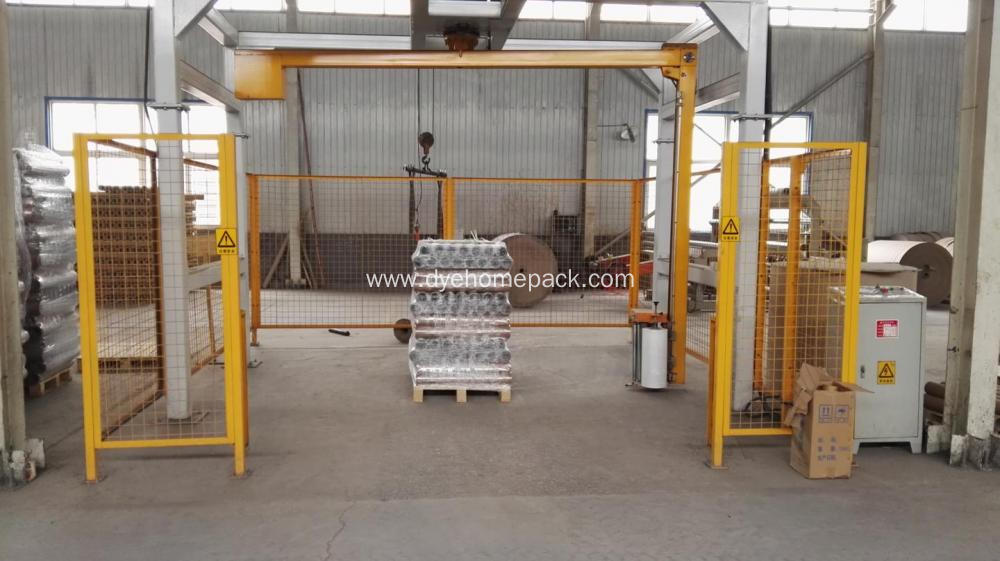 Rotary-arm conveyor pallet wrapper